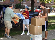 Staff members helps student move in.